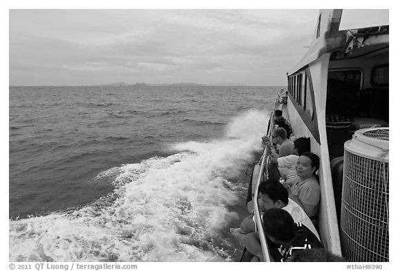 Passengers sitting on side of boat. Krabi Province, Thailand (black and white)