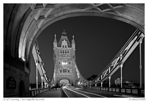 Arch and car traffic on the Tower Bridge at night. London, England, United Kingdom (black and white)