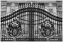 Entrance grids of Buckingham Palace with royalty emblems. London, England, United Kingdom ( black and white)
