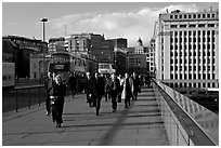 Office workers pouring out of the city of London across London Bridge, late afternoon. London, England, United Kingdom ( black and white)