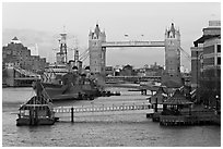 Historic boats, quays along the Thames, and Tower Bridge, late afternoon. London, England, United Kingdom ( black and white)