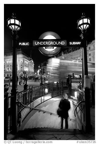 Man entering underground, and motion-blurred double decker bus,  Piccadilly Circus. London, England, United Kingdom (black and white)