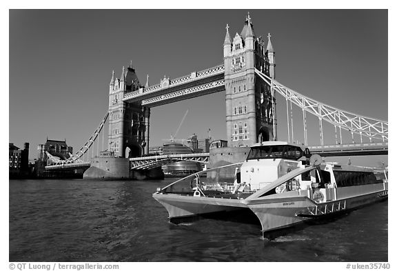 Fast catamaran cruising the Thames, with Tower Bridge in the background. London, England, United Kingdom (black and white)