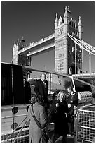 Passengers disembarking a boat in their morning commute, Tower Bridge in the background. London, England, United Kingdom (black and white)