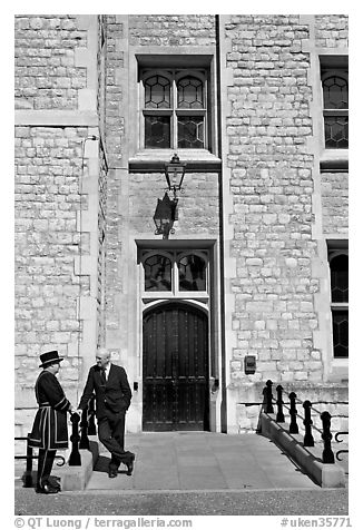 Yeoman Warder talking with man in suit in front of the Jewel House, Tower of London. London, England, United Kingdom (black and white)