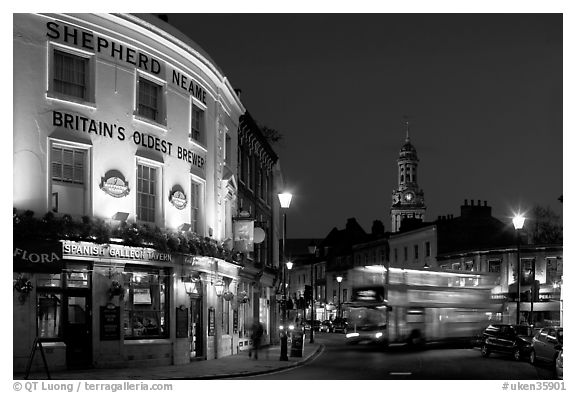 Tavern, moving double decker bus, and church at night. Greenwich, London, England, United Kingdom (black and white)