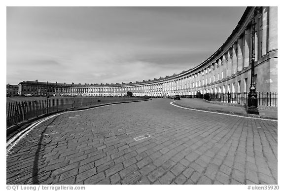 Cobblestone pavement and curved facade of Royal Crescent. Bath, Somerset, England, United Kingdom (black and white)