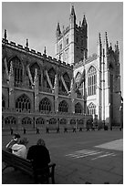 Young people sitting on a bench in a square below Bath Abbey. Bath, Somerset, England, United Kingdom (black and white)