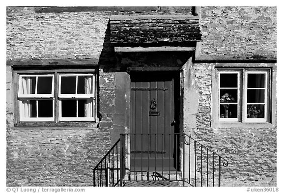 Windows and doorway entrance of stone house, Lacock. Wiltshire, England, United Kingdom (black and white)