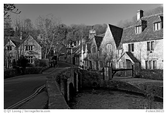 Packbridge crossing the Bybrook River and main street, Castle Combe. Wiltshire, England, United Kingdom (black and white)