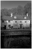 Cotswold type houses and Bybrook River, Castle Combe. Wiltshire, England, United Kingdom (black and white)