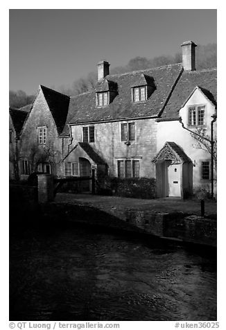 Cotswold type cottages and Bybrook River, Castle Combe. Wiltshire, England, United Kingdom (black and white)