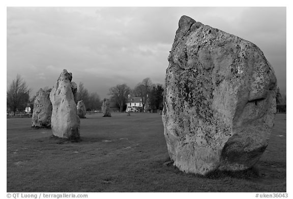 Standing stone circle and village house at dusk, Avebury, Wiltshire. England, United Kingdom