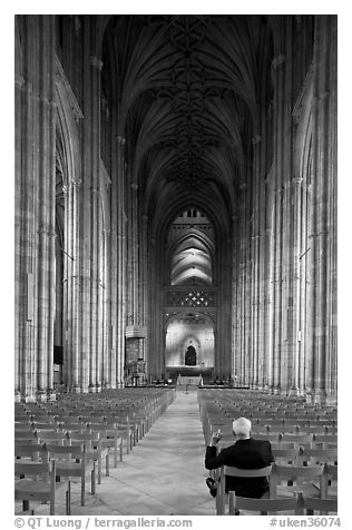 Man sitting in the Nave of the Canterbury Cathedral. Canterbury,  Kent, England, United Kingdom (black and white)