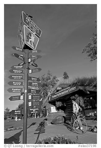Sign Air Crossroads of the World, man on bicycle in front of visitor center. Anchorage, Alaska, USA (black and white)