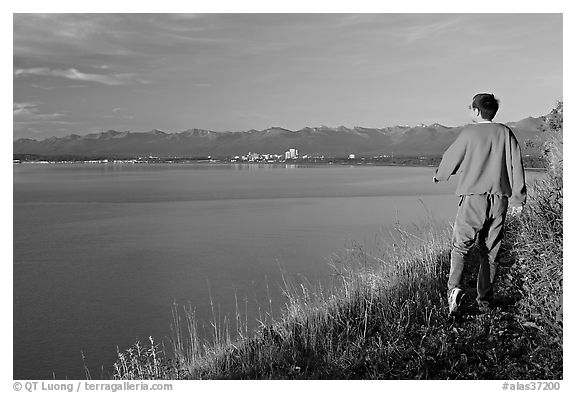 Man walking on the edge of Knik Arm in Earthquake Park, sunset. Anchorage, Alaska, USA (black and white)