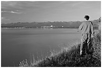 Man walking on the edge of Knik Arm in Earthquake Park, sunset. Anchorage, Alaska, USA ( black and white)