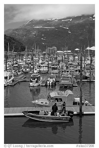 Small boat loaded at pier, harbor, and mountains. Whittier, Alaska, USA (black and white)