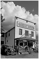 Ma Johnson hotel with classic car parked by, afternoon. McCarthy, Alaska, USA (black and white)