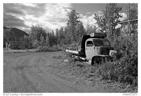 Side street with wrecked truck. McCarthy, Alaska, USA (black and white)