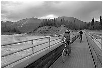 Mountain bikers crossing Kennicott River Footbridge at sunset. McCarthy, Alaska, USA (black and white)