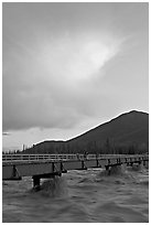 Footbridge with the Kennicott River swelled from the annual Hidden Lake flood. McCarthy, Alaska, USA (black and white)