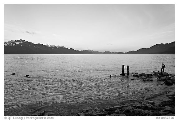 Boy standing in front of Resurrection Bay, sunset. Seward, Alaska, USA (black and white)