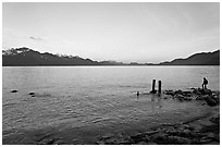 Boy standing in front of Resurrection Bay, sunset. Seward, Alaska, USA ( black and white)