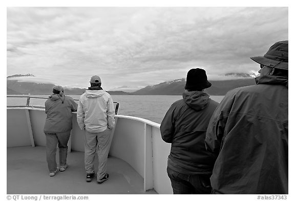 Passengers standing on deck with colorful  clothes. Seward, Alaska, USA (black and white)