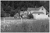 White picket fence and houses with pastel trims. Seward, Alaska, USA (black and white)