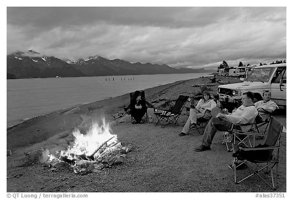 Sitting by campfire at midnight, waterfront campground. Seward, Alaska, USA (black and white)