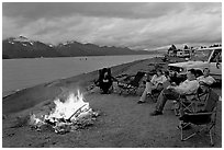 Sitting by campfire at midnight, waterfront campground. Seward, Alaska, USA ( black and white)