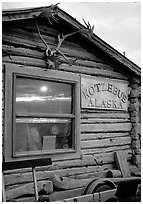 Log cabin with caribou antlers and sun reflected in window. Kotzebue, North Western Alaska, USA (black and white)
