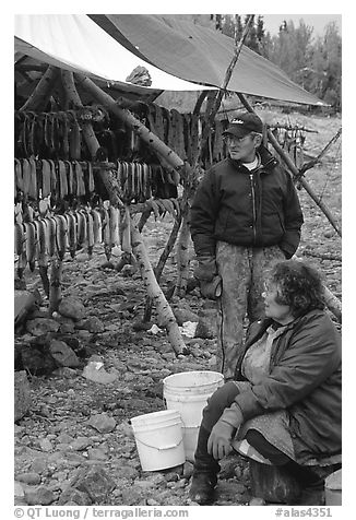 Inupiaq Eskimo man and woman next to fish hung for drying, Ambler. North Western Alaska, USA