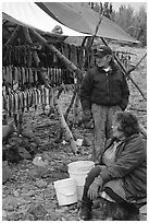 Inupiaq Eskimo man and woman next to fish hung for drying, Ambler. North Western Alaska, USA (black and white)