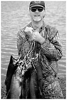 Fisherman carrying salmon freshly caught in the Fishing Hole. Homer, Alaska, USA ( black and white)