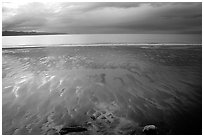 Sand patterns and stormy skies on the Bay. Homer, Alaska, USA ( black and white)