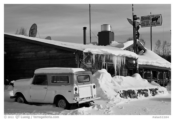 Old truck parked next to lodge in winter. Alaska, USA (black and white)