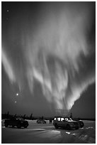 Northern Lights dance above snowy parking lot. Alaska, USA (black and white)
