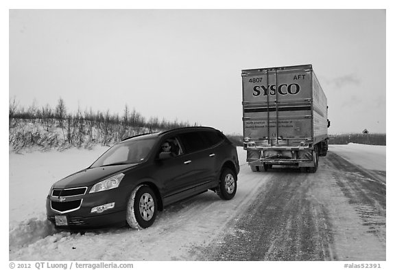 Commercial truck towing car, Dalton Highway. Alaska, USA (black and white)