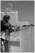 Sculptor using electric saw to carve ice. Fairbanks, Alaska, USA (black and white)