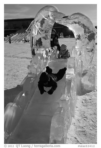 Children slide through ice sculpture. Fairbanks, Alaska, USA (black and white)