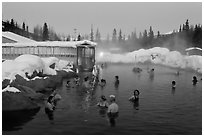 People soaking in outdoor hot springs pool in winter. Chena Hot Springs, Alaska, USA ( black and white)