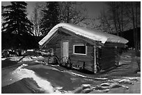 Snowy log cabin at night. Chena Hot Springs, Alaska, USA ( black and white)