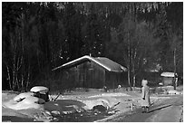 Woman with winter coat walking on path to cabins. Chena Hot Springs, Alaska, USA ( black and white)