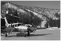 Plane with engine block warmers on frozen runway. Chena Hot Springs, Alaska, USA (black and white)