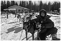 Woman dog musher posing with dog team. Chena Hot Springs, Alaska, USA (black and white)