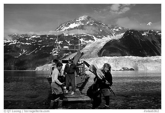 Kayakers unloading kayak from water taxi boat at Black Sand Beach. Prince William Sound, Alaska, USA (black and white)
