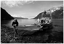 Man and woman carry kayak out of small boat at Black Sand Beach. Prince William Sound, Alaska, USA ( black and white)