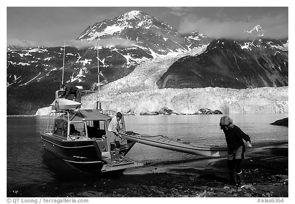 Man and woman  unload  kayak from the water taxi boat at Black Sand Beach. Prince William Sound, Alaska, USA (black and white)